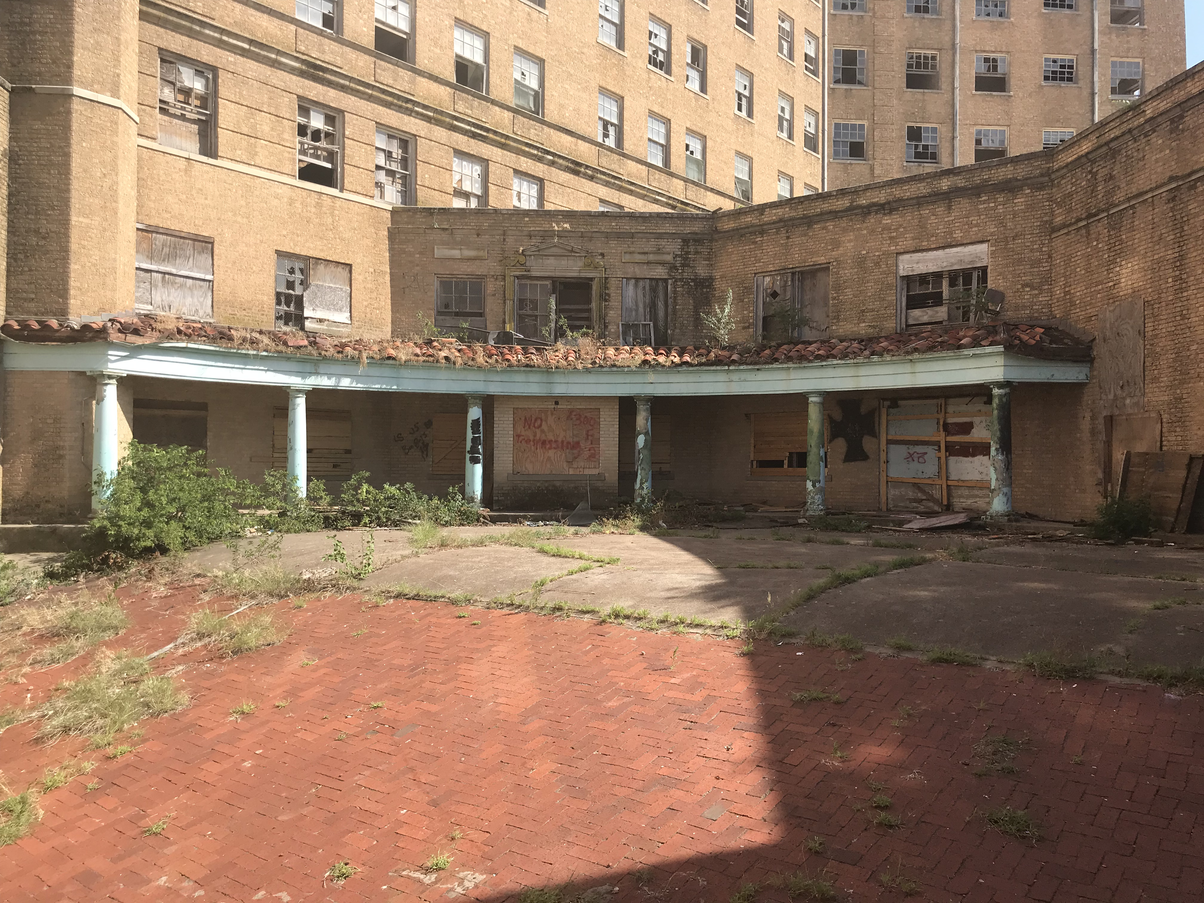 side shot of the baker hotel with overgrown weeds