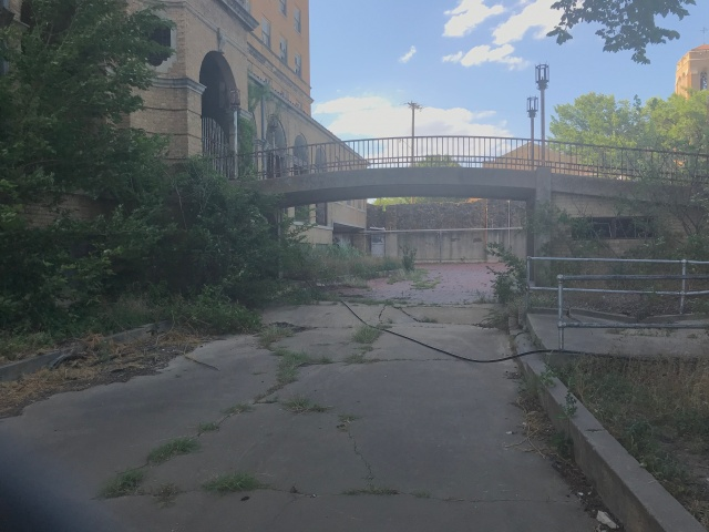bridge at an old abandoned hotel with overgrown weeds