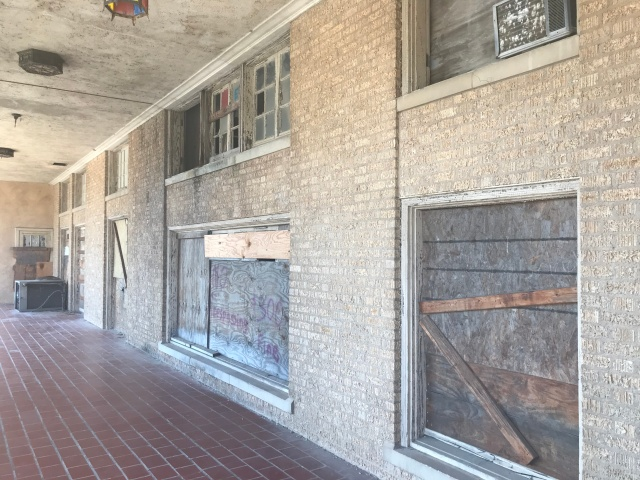 picture of boarded up windows at an abandoned hotel