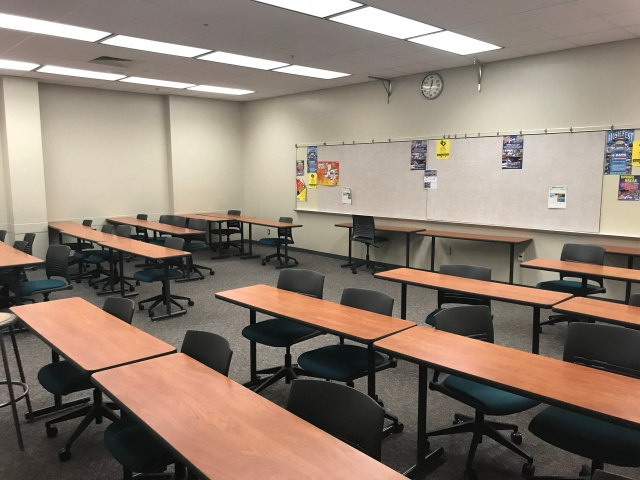 picture of a college classroom with chairs and desks