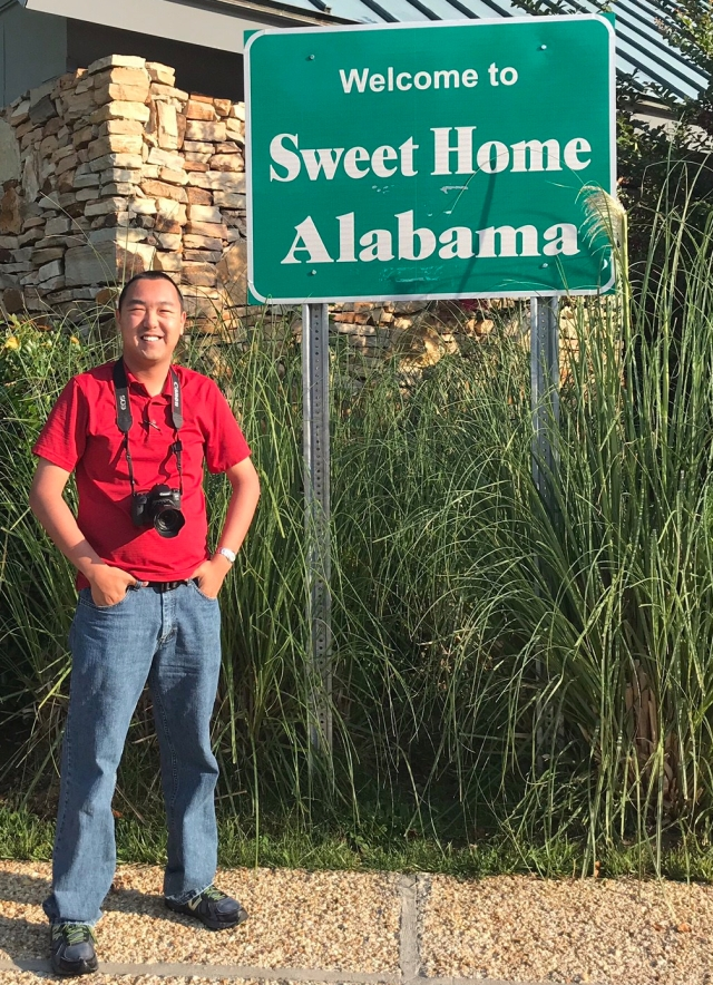 picture of a man standing by Alabama welcome sign